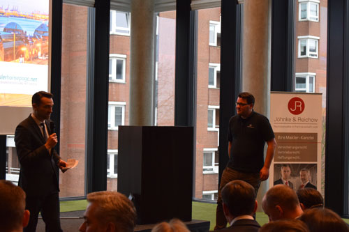 Der Moderator kündigt Björn Petersen mit seinem Vortrag zur Gestaltung von Makler-Homepages an.